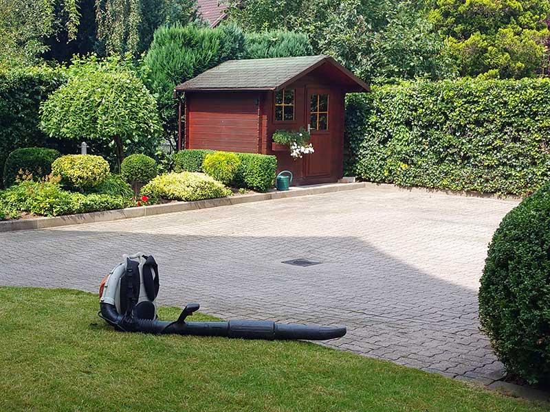 Garten mit Gartenhaus und Stihl Laubbläser nach Gartenpflegearbeiten in einem Hamburger Garten