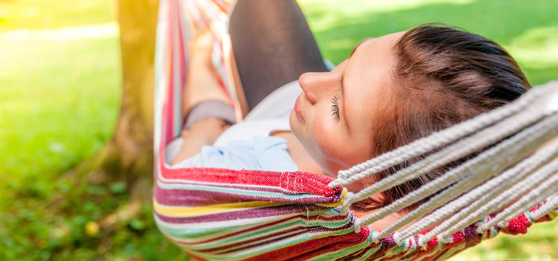 Frau entspannt im Garten in der Hängematte