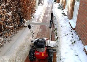 Schneeräumung einer Zuwegung mit Kehrbesen