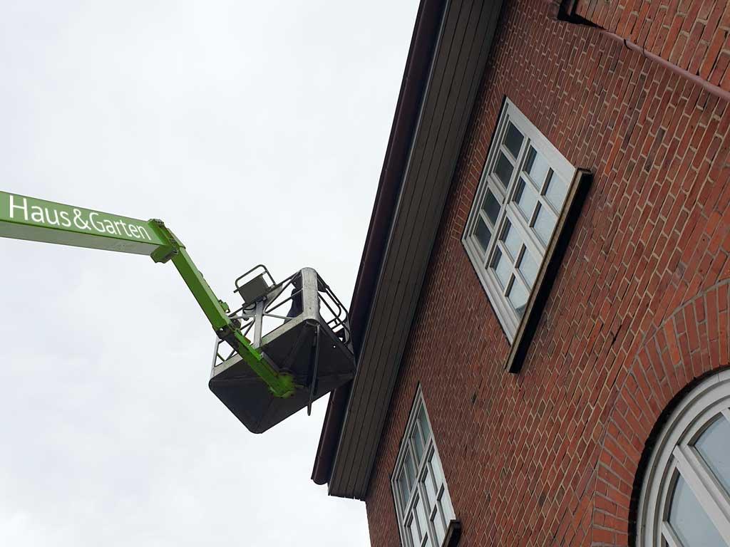 Regenrinnenreinigung mit LKW-Hubsteiger für schwer erreichbare Regenrinnen in Hamburg.