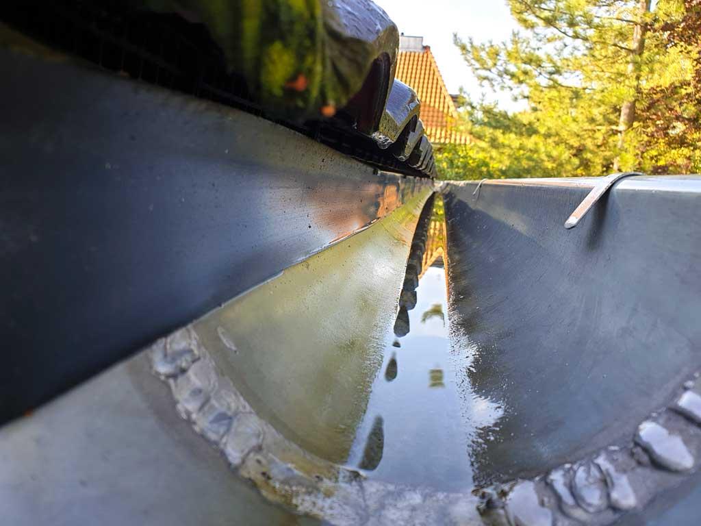 Gespülte Dachrinne nach einer gründlichen Regenrinnenreinigung befreit Laub, Moos und Schmutz